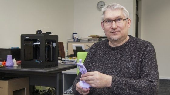 Piotr Burzyński, właściciel firmy Bardins z figurką wydrukowaną w technologii 3D. W tle pracuje drukarka Zortrax /fot.: ak /