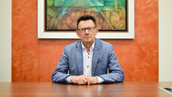 """Zbigniew Wielgosz na tle obrazu Romany Kaszczy pt. """"Dom"""". Obrazy artystki z Barlinka spotkać można w wielu oddziałach GBS Banku."""